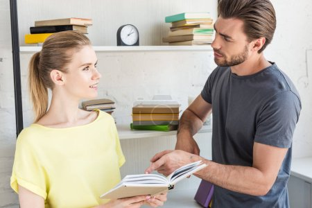 young man pointing by finger at book page to smiling girlfriend in front of shelves with books