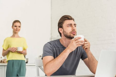 thoughtful young man sitting with coffee cup at table with laptop and his girlfriend standing behind at kitchen