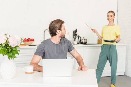 young man working at table with laptop and his girlfriend standing behind with frying pan and spatula