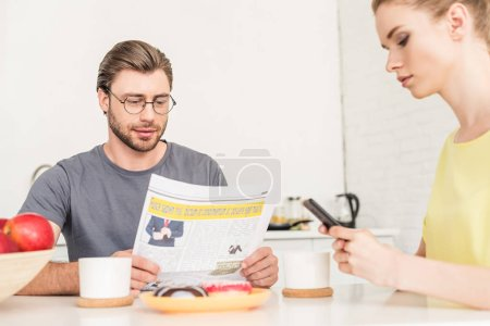 woman using smartphone and boyfriend reading newspaper at table with coffee cups and donuts