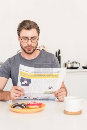 man in eyeglasses reading newspaper at table with donuts and coffee cup