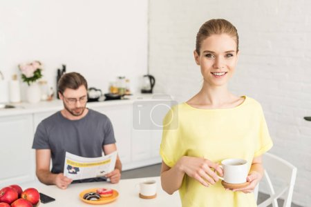 attractive smiling woman holding coffee cup and her boyfriend sitting at table and reading newspaper at kitchen