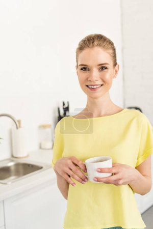 young smiling woman holding coffee cup at kitchen