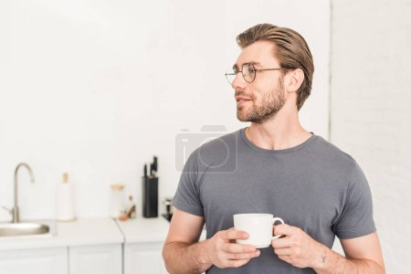 side view of smiling young man in eyeglasses drinking coffee at kitchen