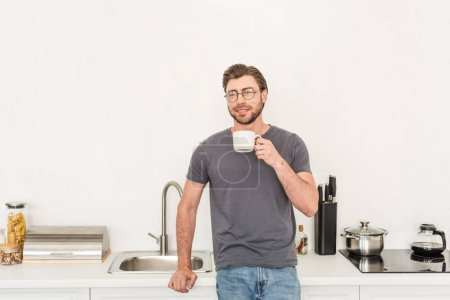 front view of smiling young man in eyeglasses drinking coffee at kitchen