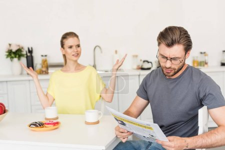 young woman with wide arms looking at boyfriend while he reading newspaper at table with breakfast