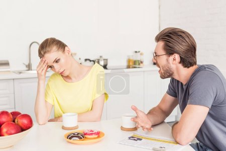 angry man screaming at upset girlfriend while she sitting at table with breakfast