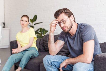 Foto de Joven molesto en gafas y novia sentado en el sofá detrás en casa - Imagen libre de derechos