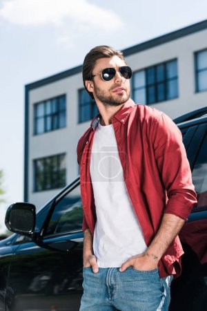 Photo for Stylish male model in sunglasses with hands in pockets standing near black car - Royalty Free Image