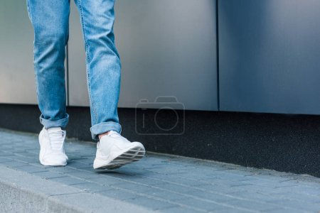 partial view of stylish male legs in jeans and white sneakers on asphalt