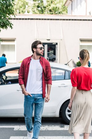 Photo for Stylish man and woman walking on crosswalk at urban street - Royalty Free Image