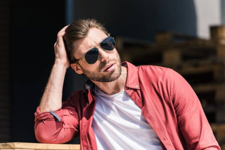 portrait of stylish young man in sunglasses holding hand on haircut