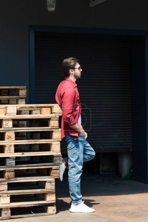 side view of young stylish man in sunglasses standing near wooden pallets