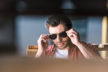 young stylish man standing near wooden pallets and adjusting sunglasses