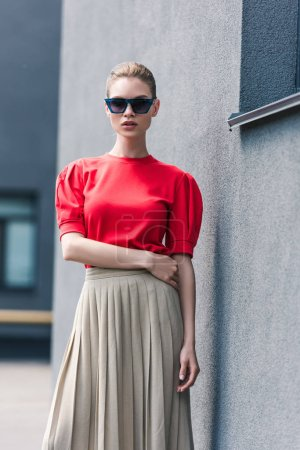 stylish female model in sunglasses posing near building