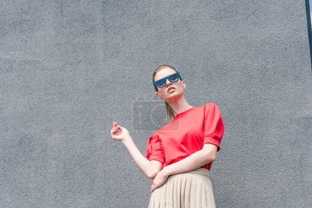 low angle view of stylish young female model in sunglasses in front of stone wall