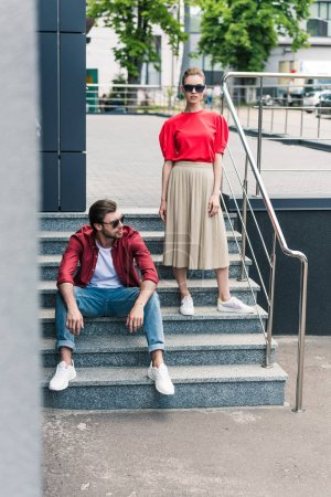 Photo for Young stylish couple of models in sunglasses on stairs at urban street - Royalty Free Image