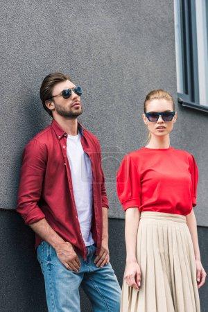 Photo pour Élégant jeune couple de modèles en lunettes de soleil posant près du bâtiment - image libre de droit