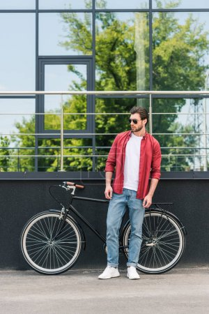 stylish young man in sunglasses standing near bicycle at city street