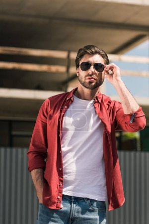 front view of young stylish man adjusting sunglasses in front of construction building