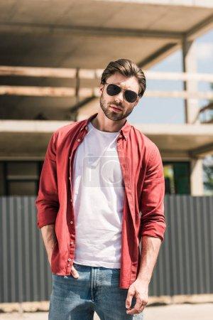 Photo pour Portrait de jeune homme élégant en lunettes de soleil posant devant le bâtiment de construction - image libre de droit