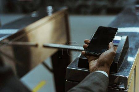 Vue rapprochée d'homme d'affaires payant tarif transports publics via smartphone