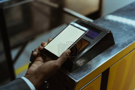 Close-up view of african american man paying public transport fare via smartphone