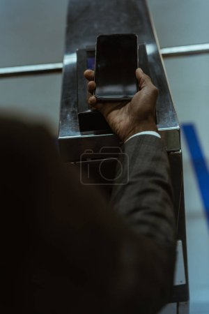 Cropped view of male hand with smartphone paying for public transport ticket