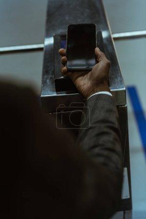 Recadrée vue de main mâle avec smartphone payer pour le billet de transport public