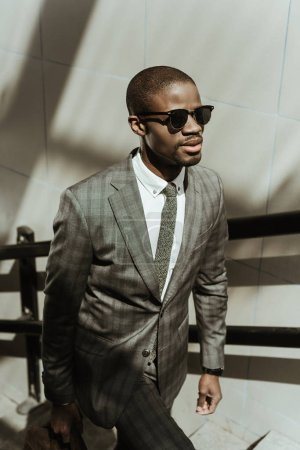 Young african american businessman wearing suit and sunglasses