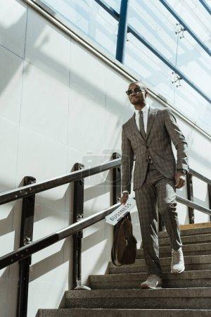 Photo pour Homme d'affaires africain américain portant costume tenant le journal et porte-documents en marchant dans les escaliers - image libre de droit