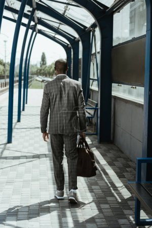 Stylish confident businessman walking on train station