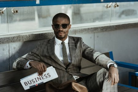 Photo for Young african american businessman in sunglasses sitting on bench - Royalty Free Image