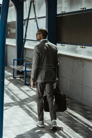 Confident businessman walking on public transport station