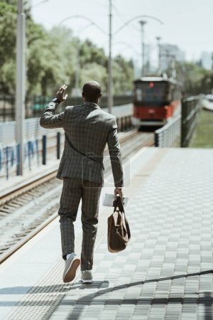 African american businessman wearing suit waiting for train on station
