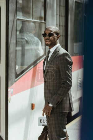 Young african american businessman waiting for train on station