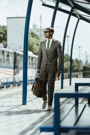 African american confident businessman walking on train station