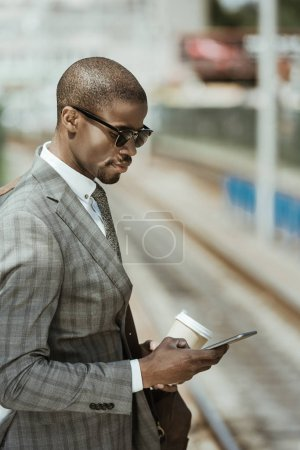 Young african american businessman with smartphone and coffee cup waiting for train