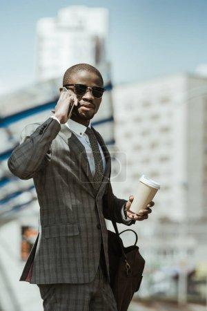 Photo pour Homme d'affaires confiant élégant parler sur smartphone et tenant la tasse de café en attente pour le train - image libre de droit