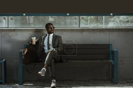 Stylish confident businessman with coffee cup sitting on train station bench