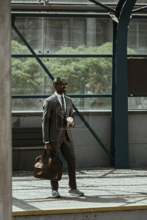 Young african american businessman with briefcase and coffee cup standing on public transport station
