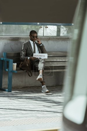 African american businessman wearing suit and holding newspaper resting on bench
