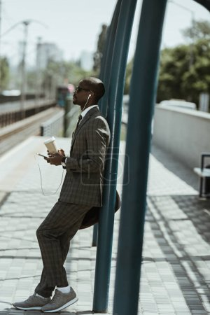 Stylish confident businessman listening to music and holding coffee cup on train station