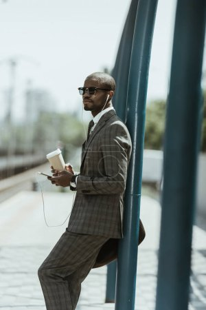 African american businessman wearing suit listening to music and holding coffee cup on public transport station