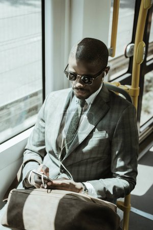 Young african american businessman listening to music while taking train