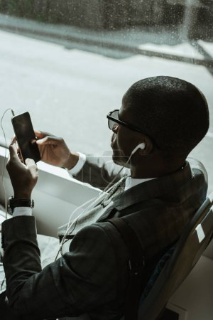 Young african american businessman in earphones using smartphone while taking train