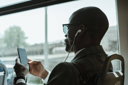 Stylish confident businessman in earphones using smartphone while taking train
