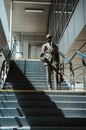 Young african american businessman using smartphone while walking on stairs