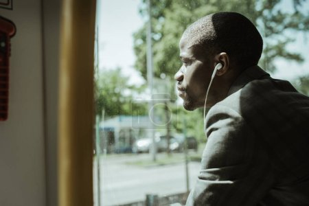 Photo for Stylish confident businessman listening to music while going to work by train - Royalty Free Image