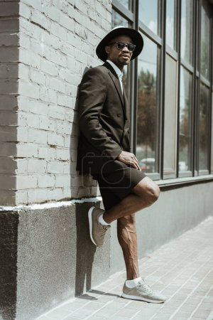 Handsome young african american man in shorts and jacket posing by building wall